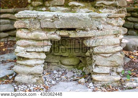 Close Up Of Old And Ancient Arch Or Niche Laid Out Of Rough Weathered Stones Partially Covered With