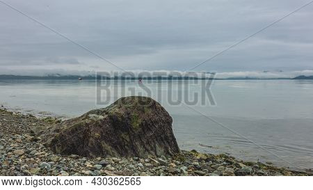 A Picturesque Boulder Lies On The Pebble Beach Of The Pacific Ocean. The Water Surface Is Calm. Ther