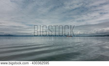 There Are Small Waves On The Smooth, Shiny Surface Of The Pacific Ocean. A Lonely Ship In The Distan