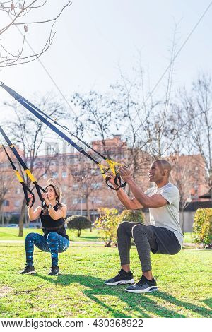 Fitness Couple Doing Legs Exercise With Fitness Straps In Park