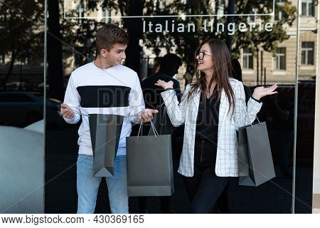 Young Couple Buyers With Shopping Bags Over Shop Window Background. Guy Looks At His Girlfriend In S