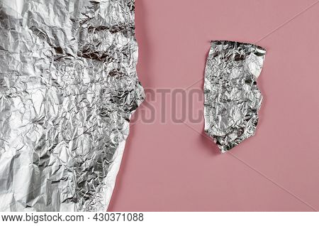 Pieces Of Crumpled Foil Against A Pink Background. Small And Large Pieces Of Aluminum Foil For Food