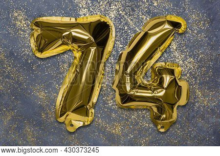 The Number Of The Balloon Made Of Golden Foil, The Number Seventy-four On A Gray Background With Seq