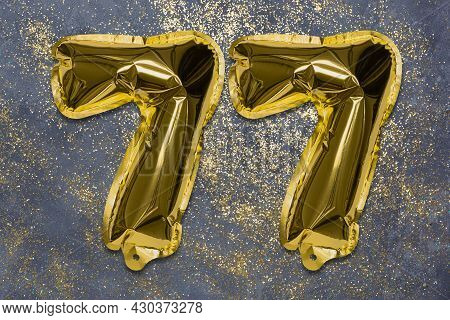 The Number Of The Balloon Made Of Golden Foil, The Number Seventy-seven On A Gray Background With Se