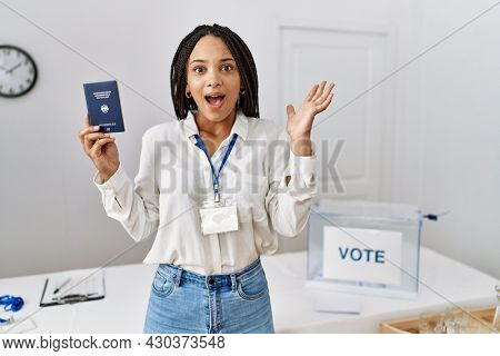 Young african american woman at political campaign election holding deutschland passport celebrating victory with happy smile and winner expression with raised hands