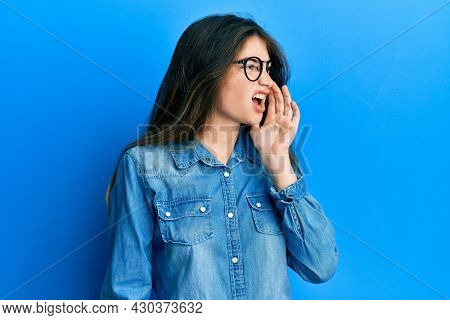 Young caucasian woman wearing casual clothes and glasses shouting and screaming loud to side with hand on mouth. communication concept.
