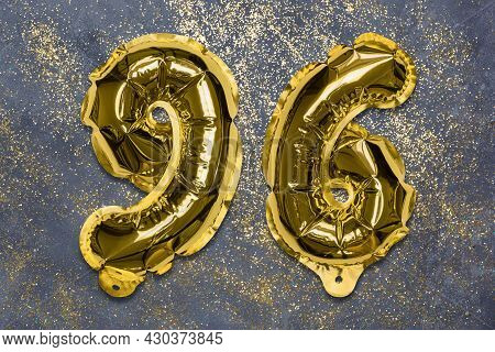 The Number Of The Balloon Made Of Golden Foil, The Number Ninety-six On A Gray Background With Sequi