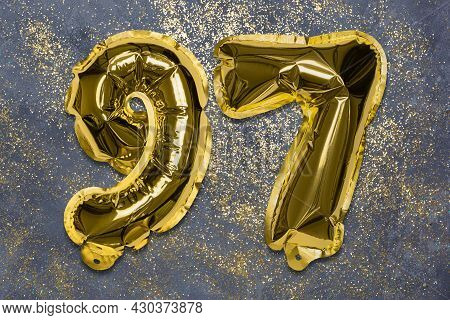 The Number Of The Balloon Made Of Golden Foil, The Number Ninety-seven On A Gray Background With Seq
