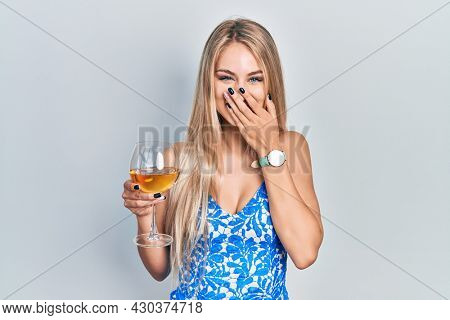 Young beautiful caucasian woman drinking a glass of white wine laughing and embarrassed giggle covering mouth with hands, gossip and scandal concept