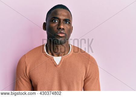 Young african american man wearing casual clothes puffing cheeks with funny face. mouth inflated with air, crazy expression.