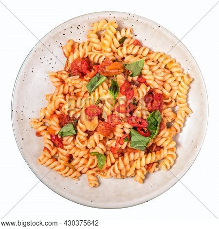 Portion Of Vegetarian Fusilli Pasta With Tomato, Basil And Hot Peppers On A Plate On A Light Table