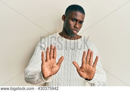 Young african american man wearing casual clothes moving away hands palms showing refusal and denial with afraid and disgusting expression. stop and forbidden.