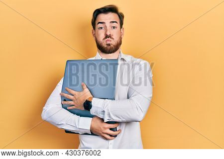 Handsome caucasian man with beard hugging laptop puffing cheeks with funny face. mouth inflated with air, catching air.