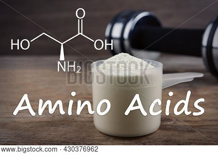 Measuring Scoop Of Amino Acids Powder On Wooden Table, Closeup