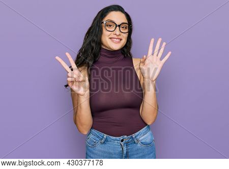 Brunette young woman wearing casual clothes and glasses showing and pointing up with fingers number seven while smiling confident and happy.