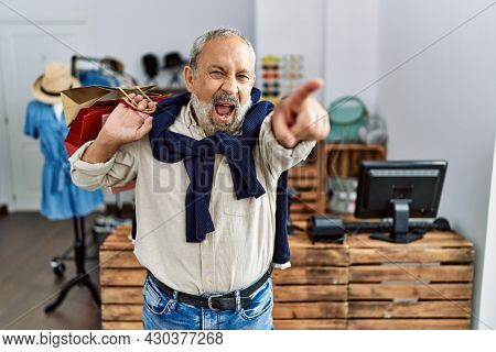 Handsome senior man holding shopping bags at boutique shop pointing displeased and frustrated to the camera, angry and furious with you