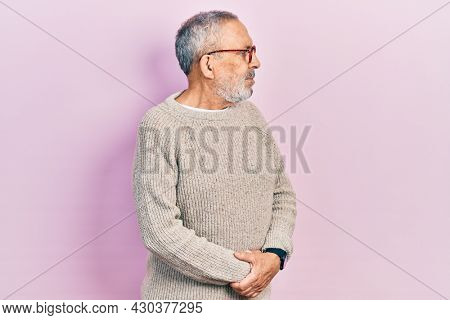 Handsome senior man with beard wearing casual sweater and glasses looking to the side with arms crossed convinced and confident