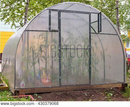 Handmade Greenhouse From A Metal Framework And A Polyethylene Film On A Farmer's Land Plot. Greenhou