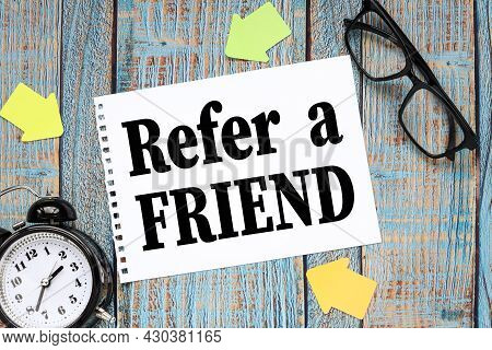 Refer A Friend. On A Blue Wooden Table A Sheet Of Notepad. Table Clock And Glasses In Black