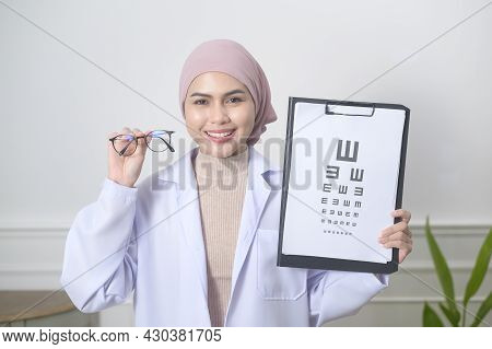 Female Muslim Ophthalmologist Holding A Vision Chart Test For Measuring Visual Acuity