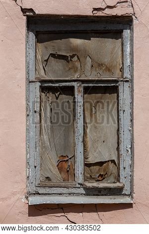 Old Wooden Window In Cracked Wall With Dirty Rag Inside