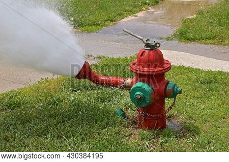A Fire Hydrant In The Process Of Being Flushed And Tested Leaves A Stream Of Water