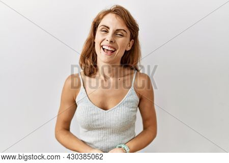 Beautiful caucasian woman standing over isolated background with hands together and crossed fingers smiling relaxed and cheerful. success and optimistic