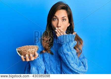 Young latin woman holding bowl with lentils covering mouth with hand, shocked and afraid for mistake. surprised expression