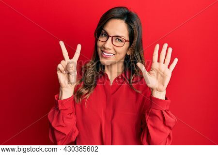 Young latin woman wearing casual clothes and glasses showing and pointing up with fingers number seven while smiling confident and happy.