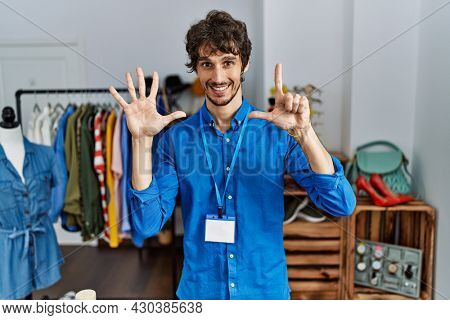 Young hispanic man working as manager at retail boutique showing and pointing up with fingers number seven while smiling confident and happy.