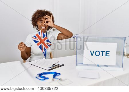 Young african american woman at political campaign election holding uk flag smiling happy doing ok sign with hand on eye looking through fingers