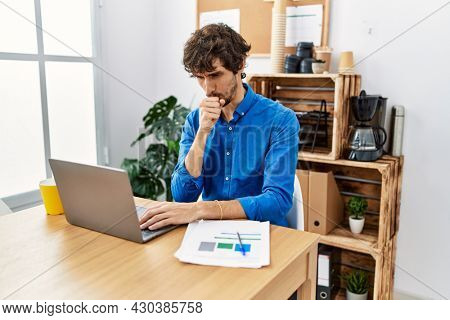 Young hispanic man with beard working at the office using computer laptop feeling unwell and coughing as symptom for cold or bronchitis. health care concept.