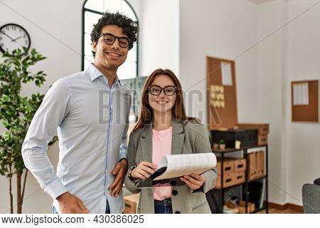 Two business workers smiling happy holding clipboard standing at the office.