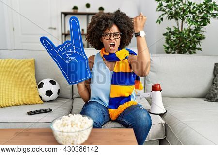African american woman with afro hair wearing team scarf cheering game holding megaphone annoyed and frustrated shouting with anger, yelling crazy with anger and hand raised