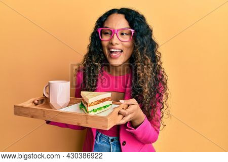 Young latin woman wearing business style having breakfast smiling and laughing hard out loud because funny crazy joke.