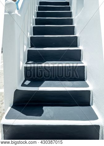 Reaching home concept. Grey stairs on exterior of whitewashed house stonewall, Mykonos island Greek Cyclades architecture. At the end of the stairway meet the house door, bellow to upper way. Vertical