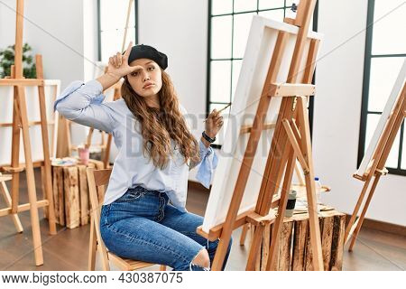 Young hispanic artist woman painting on canvas at art studio making fun of people with fingers on forehead doing loser gesture mocking and insulting.