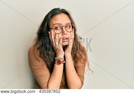 Young hispanic girl wearing casual clothes and glasses tired hands covering face, depression and sadness, upset and irritated for problem