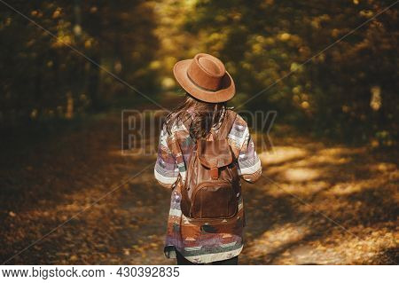 Stylish Woman With Backpack In Hat Walking In Sunny Autumn Woods. Young Female Traveler Hiking In Be