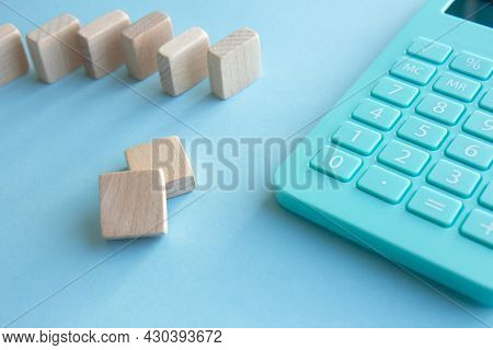 Mint Calculator And Stacks Of Wooden Cubes On Blue Background