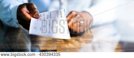 African Business Man Giving Paycheck Or Payroll Cheque