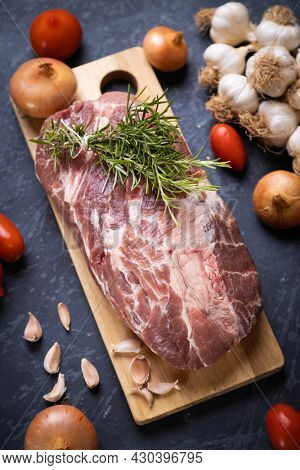 Raw pork neck meat prepared for roasting in oven or in a barbecue