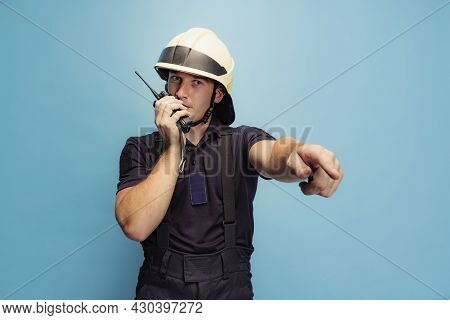 One Young Male Fireman In Uniform Giving The Directions, Coordinates Work Of Team.