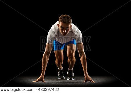 Sportive Young Man, Male Athlete, Runner Training Isolated On Dark Studio Background With Spotlight.