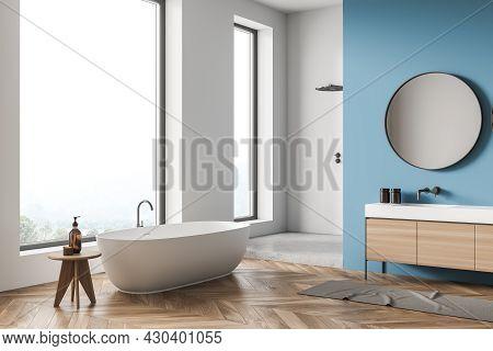 Corner Of The Panoramic White Bathroom Interior With Tub, Stool, Round Mirror, Vanity, Beige Rug, Sh