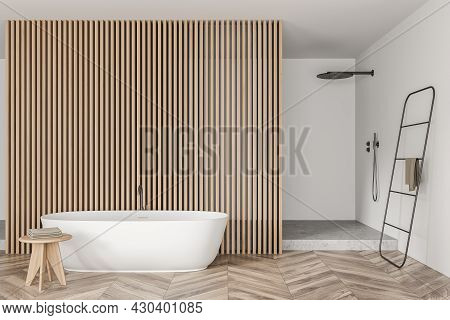 Bright Bathroom Interior With Bathtub, Towel, Closet, Shower, Partition And Oak Wooden Parquet Floor