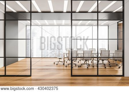 Corridor With Half Empty Panoramic Conference Room Behind The Black Framed Glass Wall Partitions. Wo