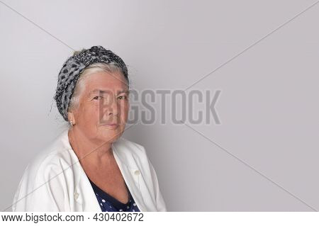 Portrait Of Attractive Cute Adult Gray-haired Woman Against Gray Background With Copy Space.