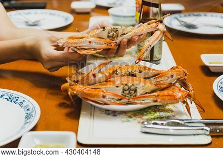 Woman Hand Holding Steamed Blue Crab At Brunch Time