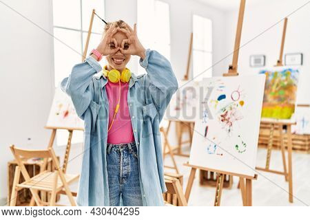 Young caucasian girl at art studio doing ok gesture like binoculars sticking tongue out, eyes looking through fingers. crazy expression.